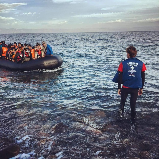 ISLA Volunteer Caleb Scott guiding in a boat of refugees on the coast of Lesvos.